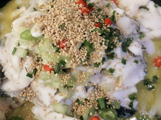 Pickled cabbage fish, put the prepared green and red peppers, chives, celery, and white sesame on the fish