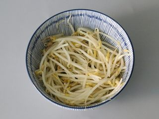After the fish fillets are boiled and blanched, the bean sprouts are picked up and placed in the bottom of a bowl and set aside.